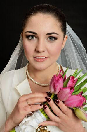 sincere girl: Beautiful, young bride with white veil and flowers bouquet. Female model in studio with black background.