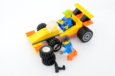 waits: WROCLAW, POLAND - FEBRUARY 28: Formula driver waits while mechanic changes tires in Lego sports car on 28th February in Wroclaw, Poland.