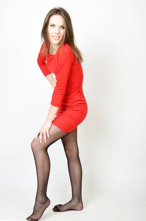 body built: Slim female model, kind girl with smiling face. Model wearing red dress and black tights. Stock Photo