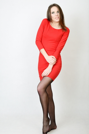 Slim female model, kind girl with smiling face. Model wearing red dress and black tights. Stock Photo