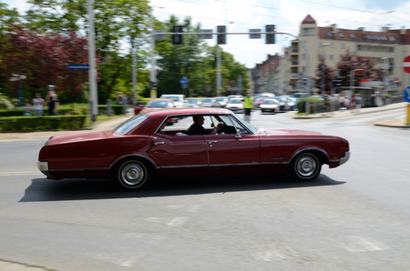 joins: WROCLAW, POLAND - MAY 21: Classic American car joins riders during Harley-Davidson parade. Few thousands motorcyclists joined Elven Bike Fest on 21 May 2016 in Wroclaw.