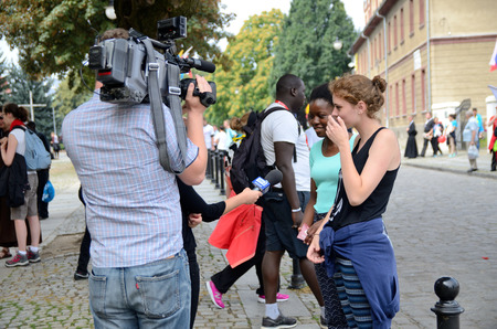 interviewed: TRZEBNICA, POLAND - JULY 25: World Youth Day, pilgrims interviewed by local TV in front of St. Jadwiga Sanctuary on 25th July 2016 in Trzebnica.
