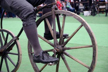 MILICZ, LOWER SILESIA, POLAND - MAY 3: Constitution Day in Poland. Performance on stage about history of bicycles. Cyclists from group Bicykle.pl from Lodz city shows old bicycles. Closeup photo of wooden wheel and legs on pedals. Cyclist with outfit from