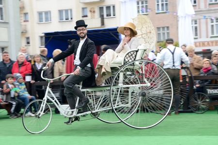 MILICZ, LOWER SILESIA, POLAND - MAY 3: Constitution Day in Poland. Performance on stage about history of bicycles. Cyclists from group Bicykle.pl from Lodz city shows old bicycles. Proud cyclist with outfit from XIX century rides tricycle with his lady on
