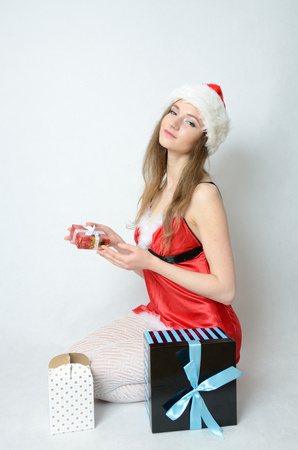 Young female model, Christmas photo session. Twenty years old girl in Santa Claus costume, holding gift box.