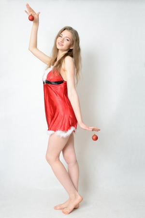Young female model, Christmas photo session. Twenty years old girl in Santa Claus costume, holding two baubles. Stock Photo