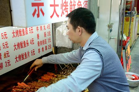 SHENZHEN, CHINA - APRIL 3: man offers spicy snacks made in deep-oil on April 3rd, 2018.