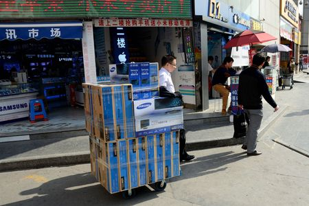 SHENZHEN, CHINA - APRIL 3: SEG famous electronic market in HuaQiangBei road. Man pushes cart with monitors on April 3rd, 2018.
