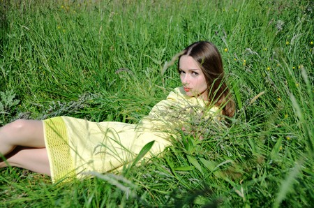 Petite woman, wearing yellow dress, laying in the grass. Female model and nature.