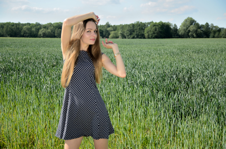 Petite woman walking in the meadow. Female model and nature.