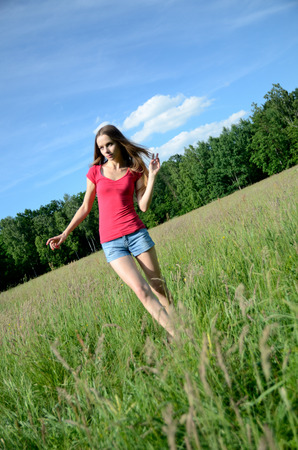 Woman with jeans shorts and red top in the meadow. Female model and nature.