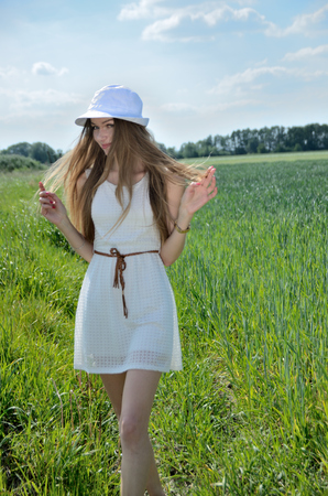Petite woman walking in the grain field. Female model wearing white dress and white hat. Stock Photo