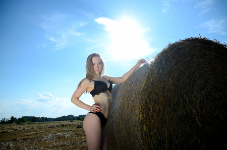 Female model from Ukraine posing in Polish farm. Young woman in underwear stands next to bale of hay.