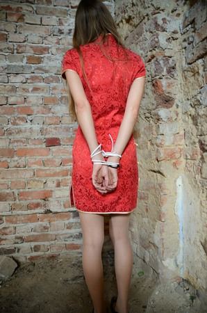 Young woman in red dress with tied hands behind her back. Indoor photo, kidnapped girl in basement, ruins.
