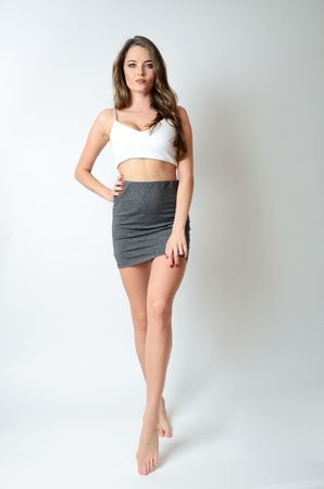 Attractive young woman with white top and short skirt in grey color. Well-built female model.