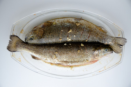Two fishes, fresh trouts on heatproof dish prepared for baking. Fishes with spices, garlic, ginger and soy sauce.