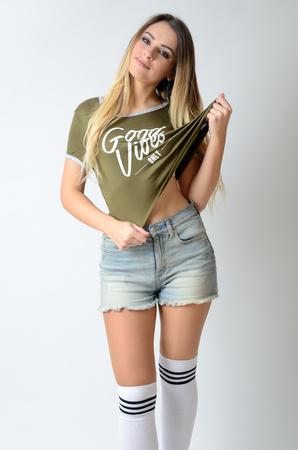 Preciosa modelo polaca con pelos rubios. Chica bien formada con calcetines, pantalones cortos y camiseta verde.