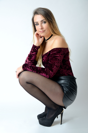 Schönes polnisches Modell. Gut gebautes Mädchen mit kastanienbraunem Top, schwarzen Shorts, High Heels und Strümpfen.