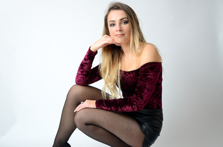 Beautiful Polish model. Well-built girl with maroon top, black shorts and stockings.