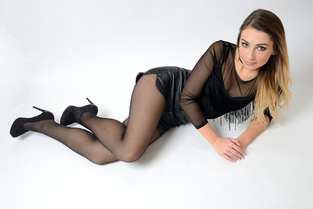 Well-built girl from Poland wearing black clothes. Young, blonde female model sitting on ground, white background.