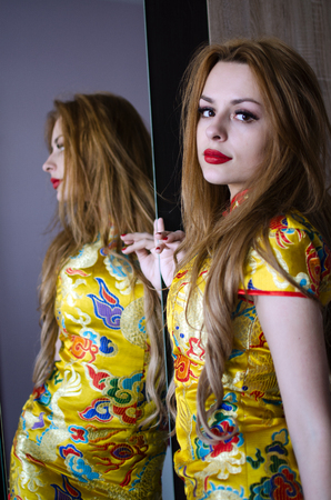 Shapely girl from Poland. Young female model posing near mirror, wearing colorful Chinese dress.