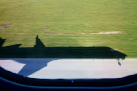 Shadow of plane during landing. Green grass surrounding airport and strong shadow, shape of plane. Wroclaw airport in Poland.  Stock Photo