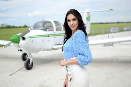 Young, elegant woman with plane. Woman stands in front of small white plane.