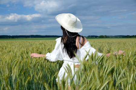Country girl with white hat surrounded by barley field. Beautiful brunette wearing white top and white shorts. Photo from behind, without face.