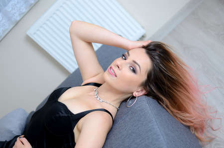 Woman in black dress laying on sofa. Her hairs falling down to the floor.
