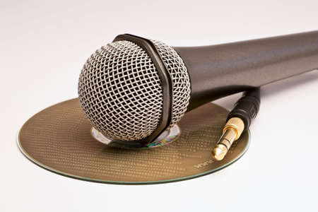 A microphone and a jack laying over a compact disk with binary code burnt out label. photo