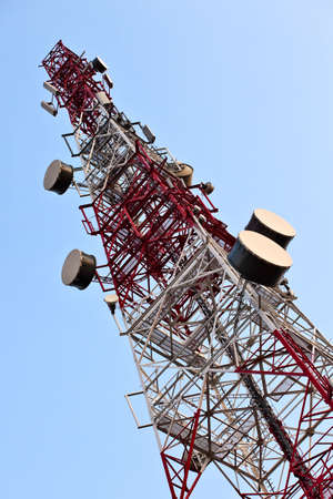 Telecommunication tower with antennas over blue sky. photo