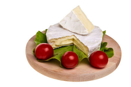 Round camembert cheese on lettuce with cherry tomatoes on cutting board. photo