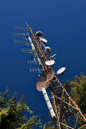 Telecommunication mast with microwave link and TV transmitter antennas over a blue sky. photo