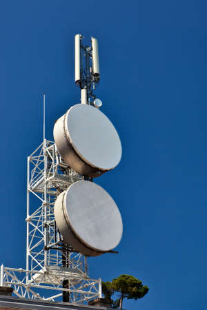 microwaves: Telecommunication mast with microwave links and cellular network antennas over a blue sky. Stock Photo