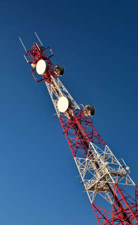 Telecommunication mast with microwave link antennas over a blue sky. photo