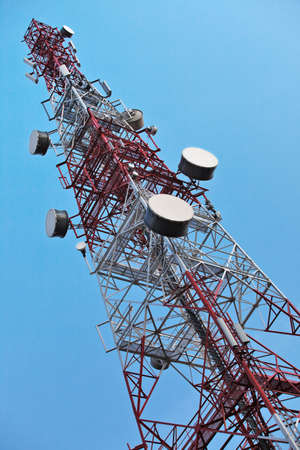 Telecommunication tower with antennas over a blue sky. Stock Photo