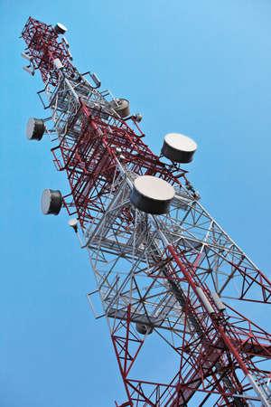 microondas: Torre de telecomunicaciones con antenas sobre un cielo azul. Foto de archivo