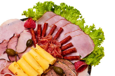 food buffet: Dish with sliced ham, cheese, salami rolls, bacon and lettuce closeup view. Stock Photo