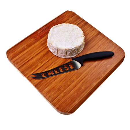 Round camembert block on wooden board with cheese knife. photo