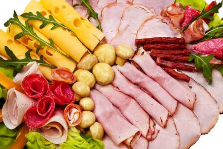 embutidos: Plato con jamón ahumado, rollos de salami y queso sobre fondo blanco. Foto de archivo