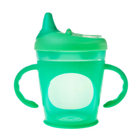 Green baby plastic cup with handles isolated over white background. photo