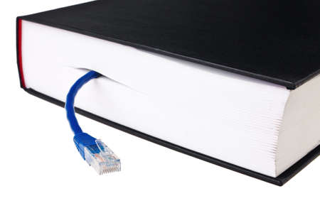 Book in hardcover with blue LAN patch cord isolated over white background. photo