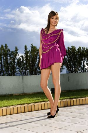 Sexy women with in dress on the building roof. Sky on the background. photo