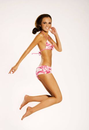 pink bikini: a beautiful brunette girl wearing bikini jumping up on white background