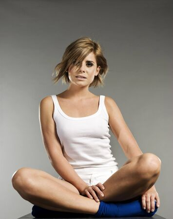 beautiful blonde woman wearing white shorts and white shirt on grey background
