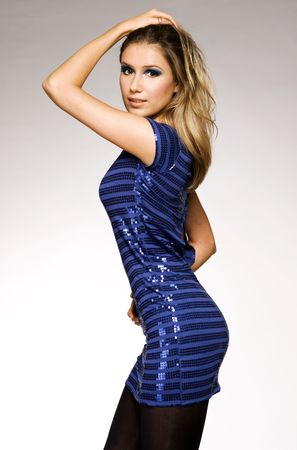 beautiful blond model in blue lucid dress posing on grey background photo