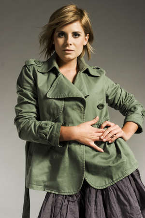 beautiful blonde model wearing green coat on grey background photo