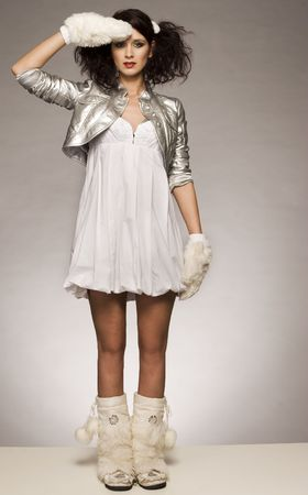 eskimo woman: beautiful brunette winter girl wearing furry gloves and boots on light background