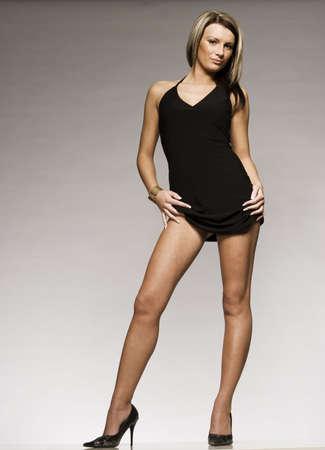 beautiful blonde girl wearing black mini dress and high heeled shoes posing on grey background photo