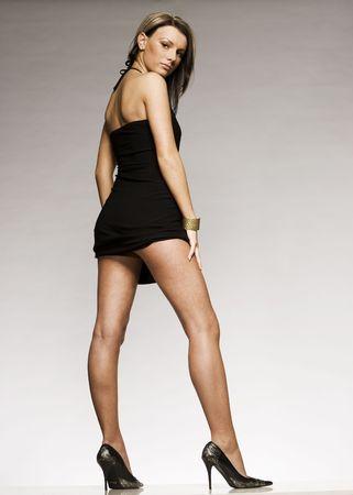 high heeled: beautiful blonde girl wearing black mini dress and high heeled shoes posing on grey background